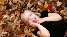 Children Playing In Autumn Leaves Photo