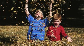Children Playing In Autumn Leaves Photo#2