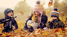 Children Playing In Autumn Leaves Wallpaper